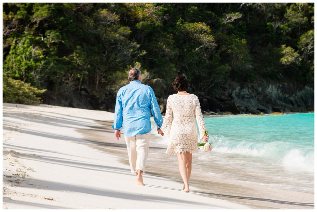 newlyweds walking the beach in st john