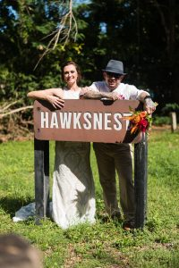 a bride and groom by the sign at hawksnest beach on st john