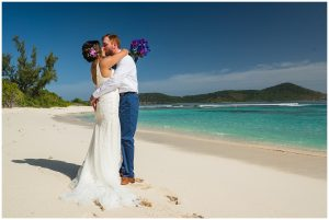 beach wedding with bride and groom on sand kissing